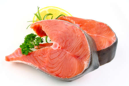 Two salmon steak with lemon, rosemary and parsley, close up