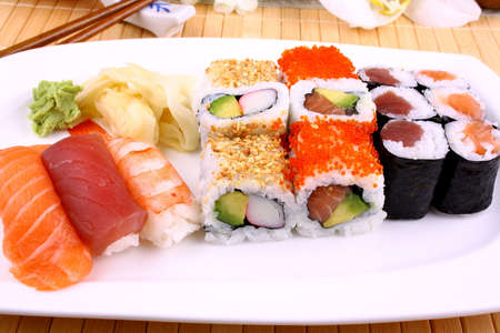 Delicious sushi, wasabi and chopsticks close up