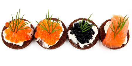 Black bread topped with salmon, trout and sturgeon caviar, close up