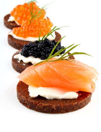 Black bread topped with salmon fish, trout and sturgeon caviar, close up photo
