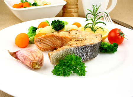 Grilled salmon steak with vegetables, close up photo