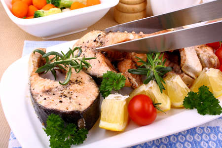 Grilled salmon steak and vegetables and with tongs, close up photo