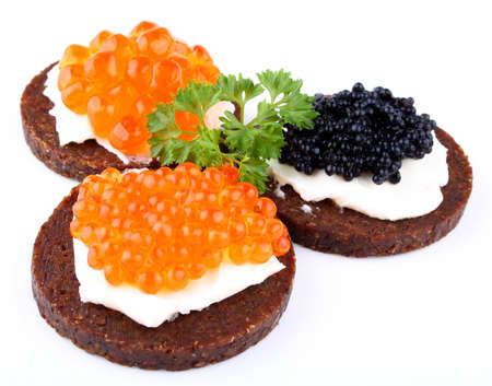 Black bread topped with salmon, trout and sturgeon caviar, close up photo