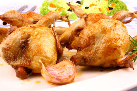 Fried quail with gravy, garlic, rosemary and salat, close up photo