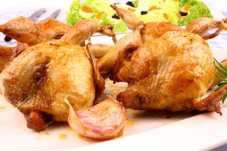 Fried quail with gravy, garlic, rosemary and salat, close up photo