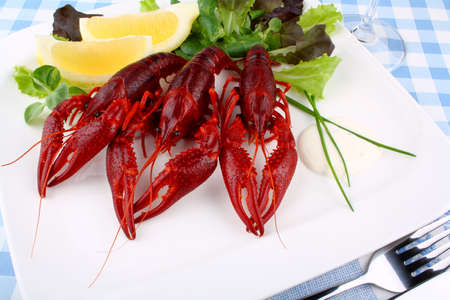 Red boiled crayfish and lettuce, lemon with cutlery, close up photo