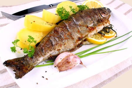 Grilled whole trout, potato, lemon and garlic, close up