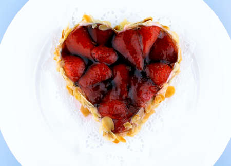 Strawberry cake with almond in heart shape, top view photo