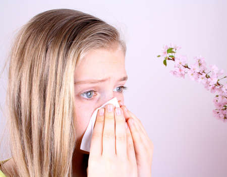 Girl blows her nose with handkerchief and cherry blossoms, allergy concept  Stockfoto