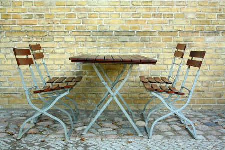 Four chairs and table in beer garden on brick wall, close up Stock Photo