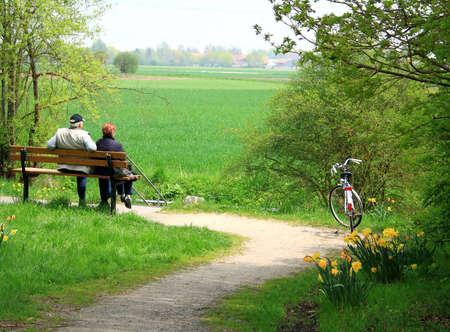 Äldre par sitter avkoppling efter cykling som bakgrund
