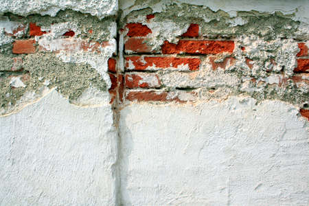 Old brick wall with broken plaster, close up photo