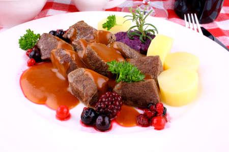 Red deer goulash with potato, Burgundy sauce and wild berries, macro Stock Photo