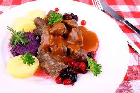 clod: Red deer goulash with potato, Burgundy sauce and wild berries, top view