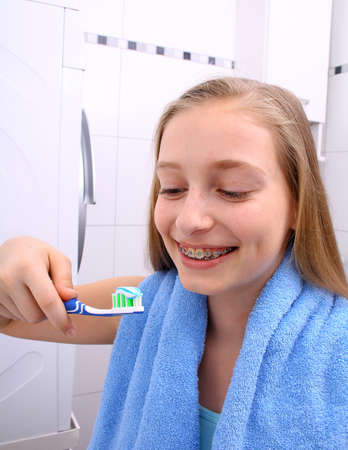 Blond girl with braces smiling while brushing your teeth, vertical photo