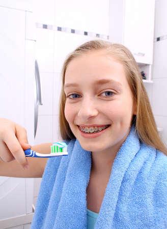 appareil dentaire: Fille blonde avec des accolades souriant pendant le brossage des dents, de près