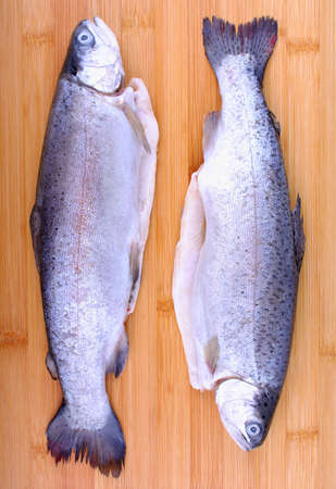 Two fresh full trout on bamboo cutting board, top view photo