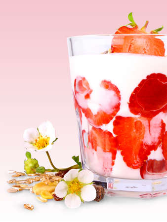 Strawberries with white yogurt in glass, flowers and cereal, pink background photo