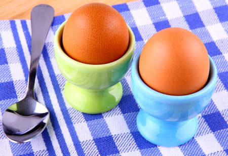 Two boiled eggs with spoon, checkered blue and white pattern photo