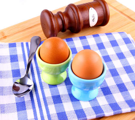 Two boiled eggs with spoon and salt, checkered blue white pattern photo