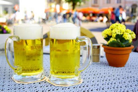 steins: Two steins beer garden in the city, soft focus