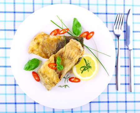 Two fried fish fillets with lemon slice on white plate, top view photo