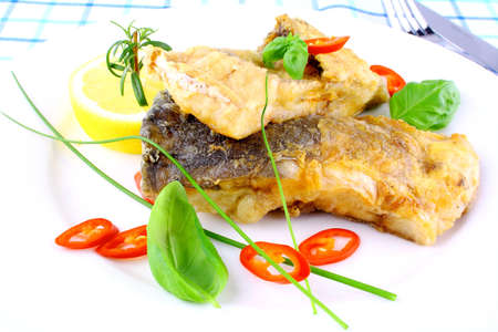 Fried fish fillets with lemon, chili peppers slice on white plate, close up photo