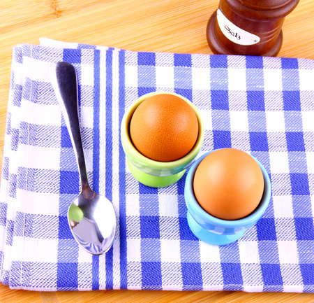 Two boiled eggs with spoon, checkered white and blue pattern photo