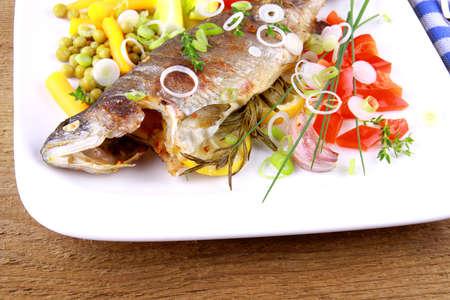 Grillad forell med ganska fina grönsaker med bestick, närbild