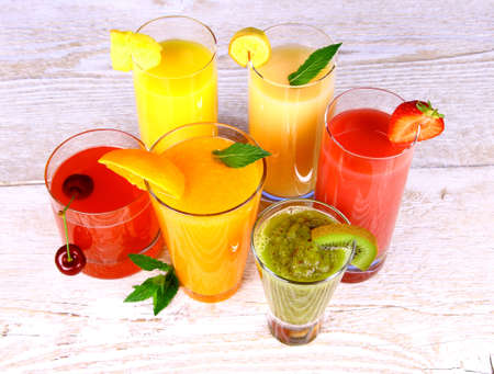 Fruit juices, kiwi, cherry, orange, strawberry, banana, pineapple, top view photo