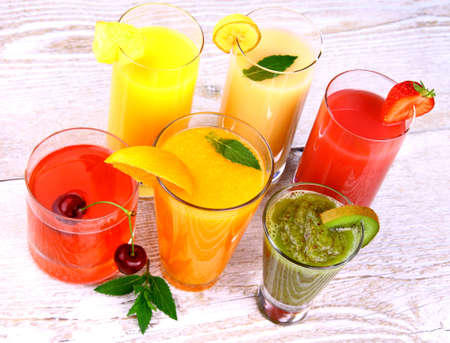 Fruit juices, kiwi, cherry, orange, strawberry, pineapple, top view photo