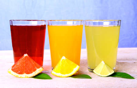 Citrus juices in glass from grapefruit, oranges, lime, horizontal photo