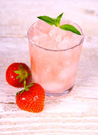 granizados: Granizado de fresa en vidrio con las frutas y la menta, enfoque suave