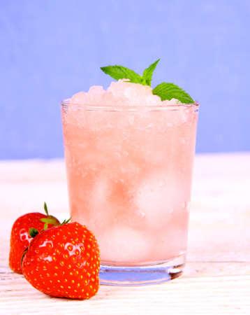 Strawberry slush with fruits and mint on blue background, close up