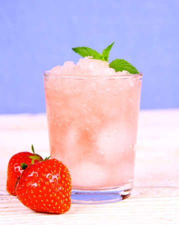 Strawberry slush with fruits and mint on blue background, close up