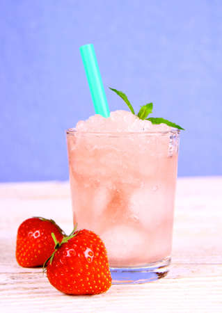 slush: Strawberry slush in glass with straw on blue background, close up