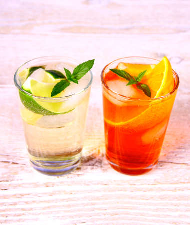 hugo: Orange and elderflower cocktails on white wooden background, close up