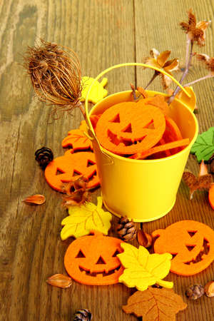 Yellow bucket with Halloween and autumn deco, close up photo