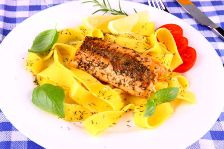 Grilled salmon fillet with taglateli, lemon and herbs, top view photo