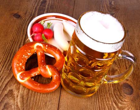 Öl med kringla, vit korv och rädisor Stockfoto