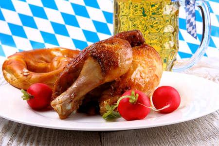 Oktoberfest chicken with radish, pretzel and beer, close up photo