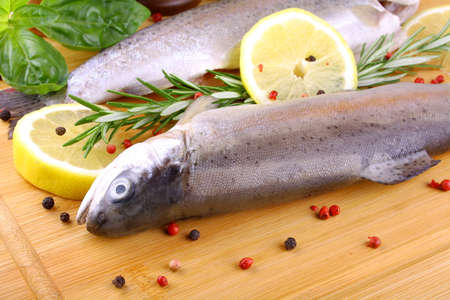 Two fresh rainbow trout with spices and lemon on bamboo board photo