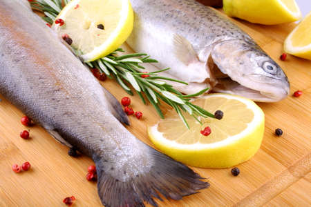 Two fresh rainbow trout with spices, red pepper and lemon, top view photo