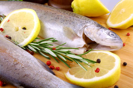 Two whole rainbow trout with rosemary, red pepper and lemon, close up photo