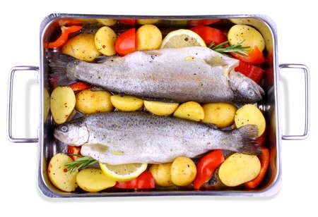 Two marinated trout with red pepper, potato, lemon, isolated photo