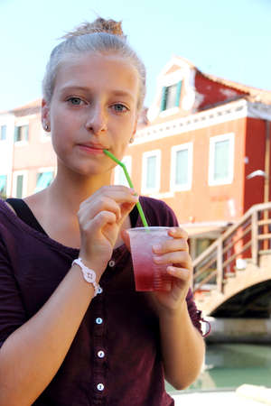 Cute girl with red slush drink, close up photo