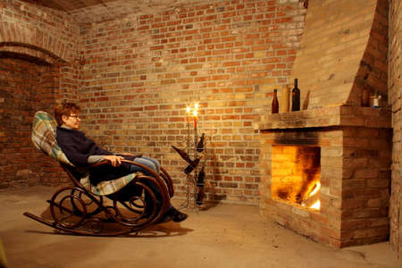 Woman in rocking chair by the fireplace with candles, horizontal photo