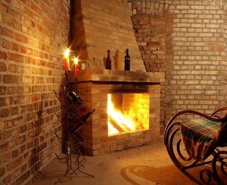 Vintage interior with rocking chair by fireplace and candles, close up photo