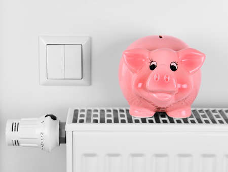 Pink piggy bank saving electricity and heating costs, close up 스톡 콘텐츠