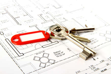 Bunch of keys with red keychains at building drawing, close up